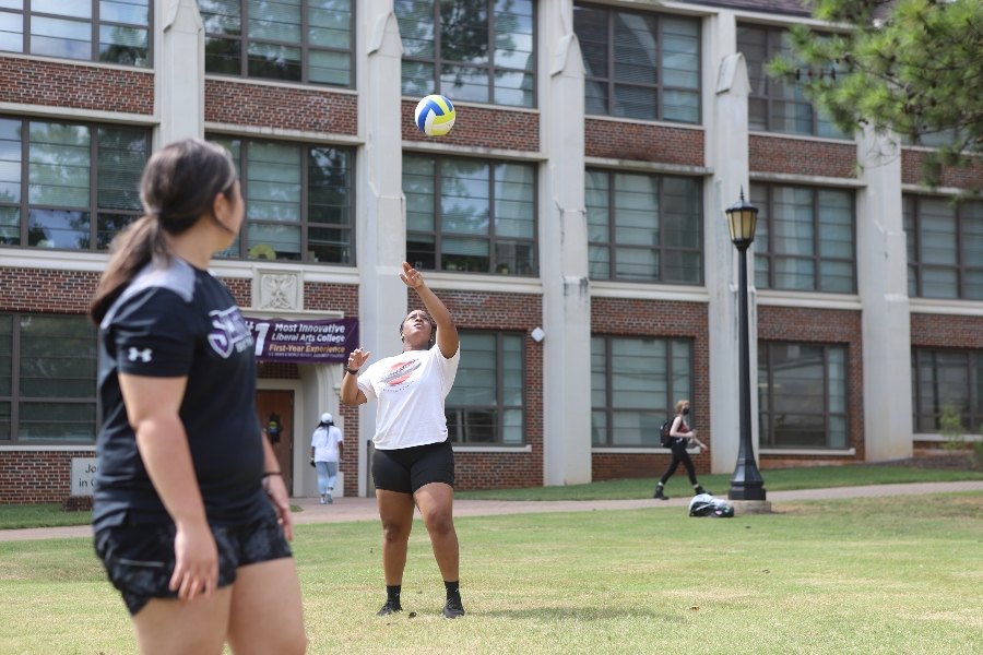 A student winds up to serve a volleyball with Campbell Hall in the background.