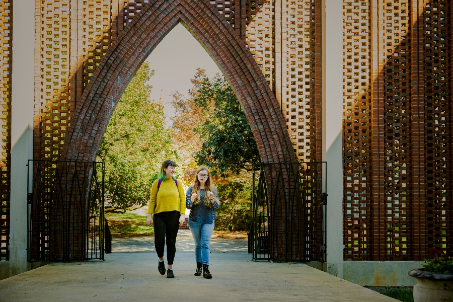 Two students walk through a decorative brick arch in front of the Dana Fine Arts Building.