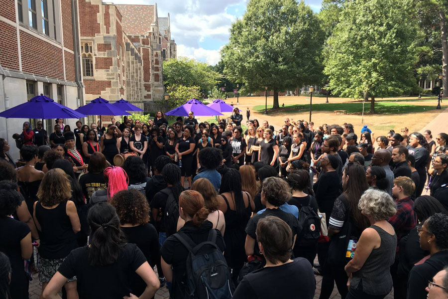 A large group of people wearing black gather outside that Alston Campus Center.