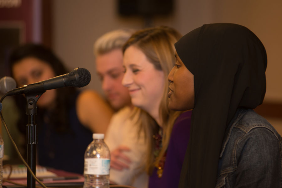 Four panelists addressing an audience. The person speaking is wearing a hijab.