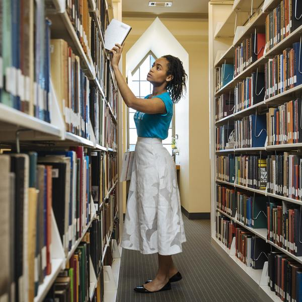 a female student pulling a book from a library shelf