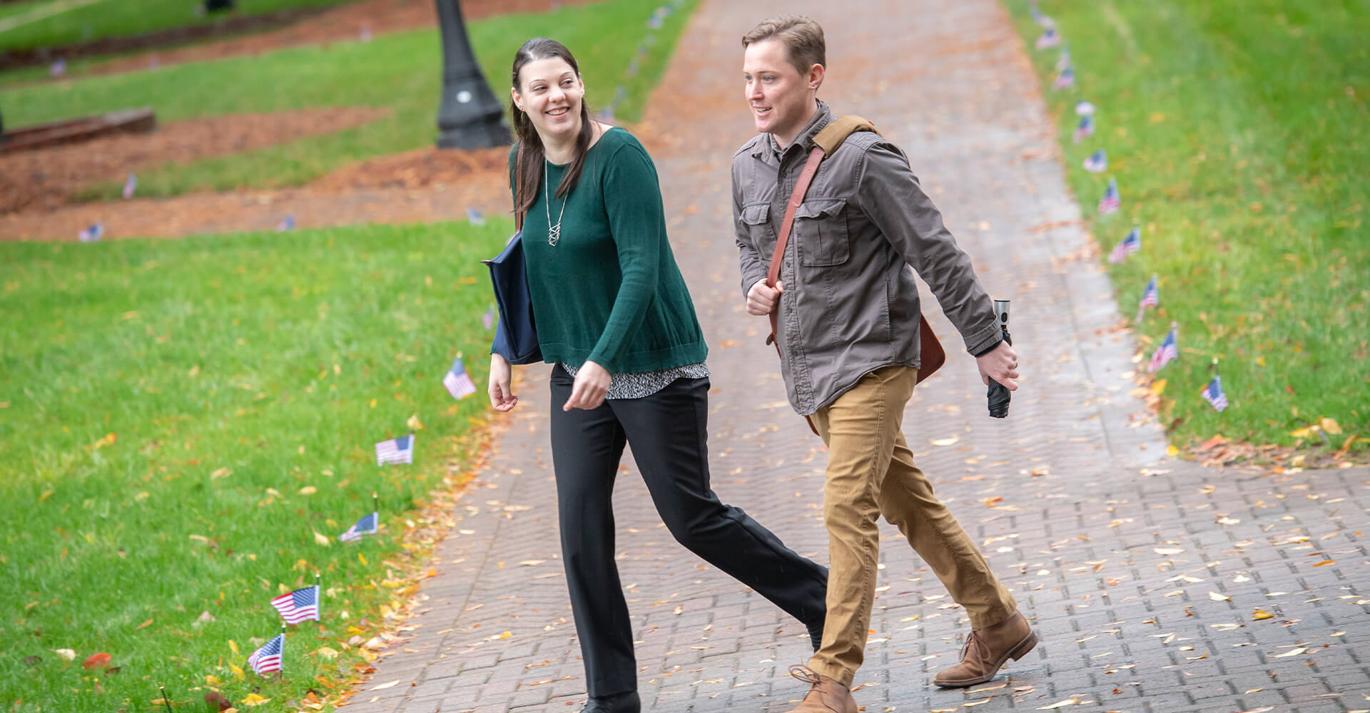 a woman and a man walking on campus