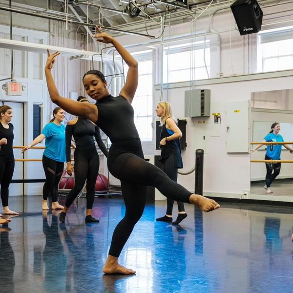 A student performing a ballet move while other students observe.