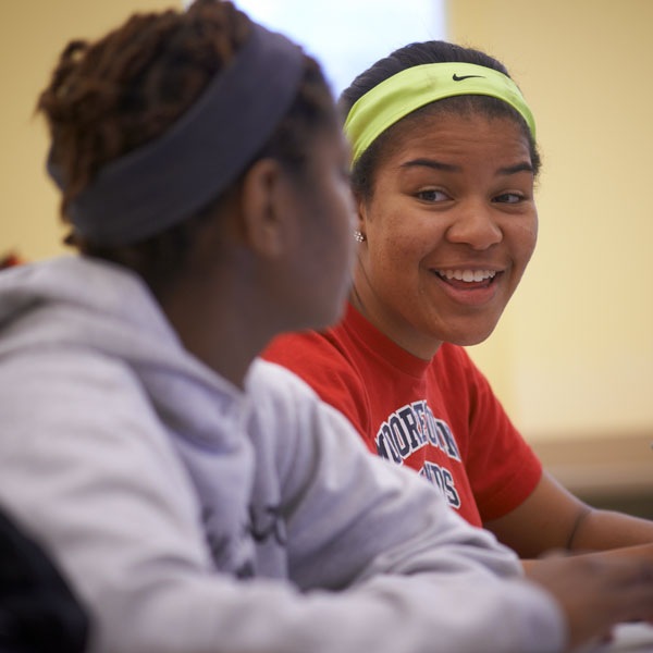 Two students smiling at each other.