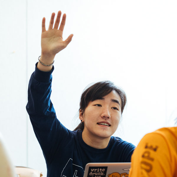 A student raises their hand in class.