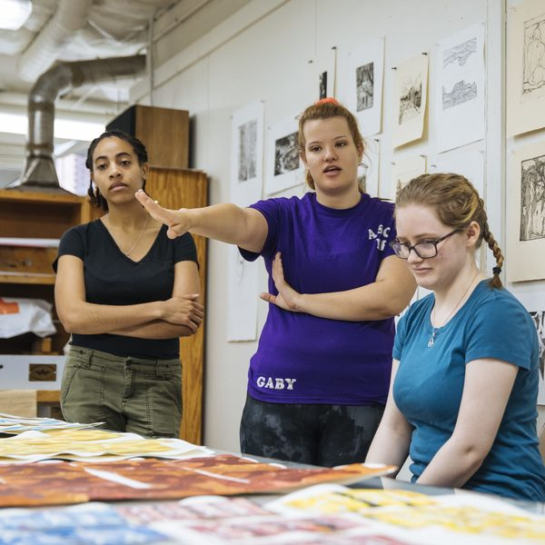 three female students discussing art pieces