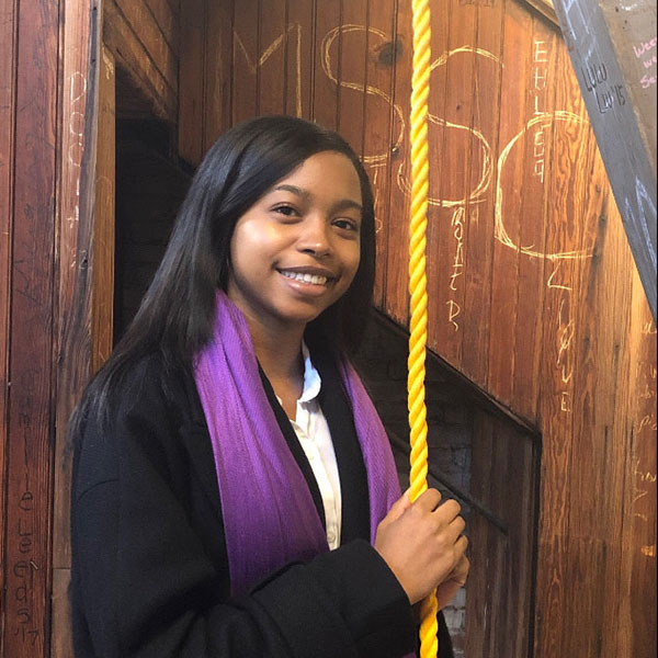 Smiling student holding rope to the bell tower