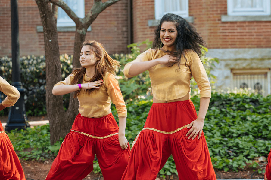 A student bollywood dance team performs outside.