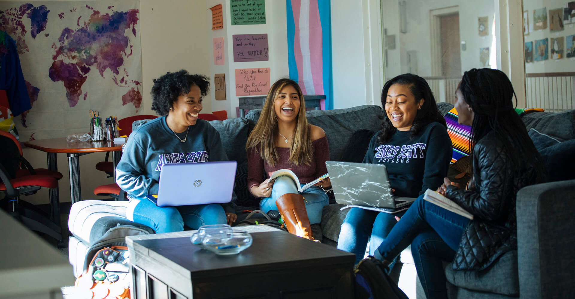 four students on a couch studying and laughing