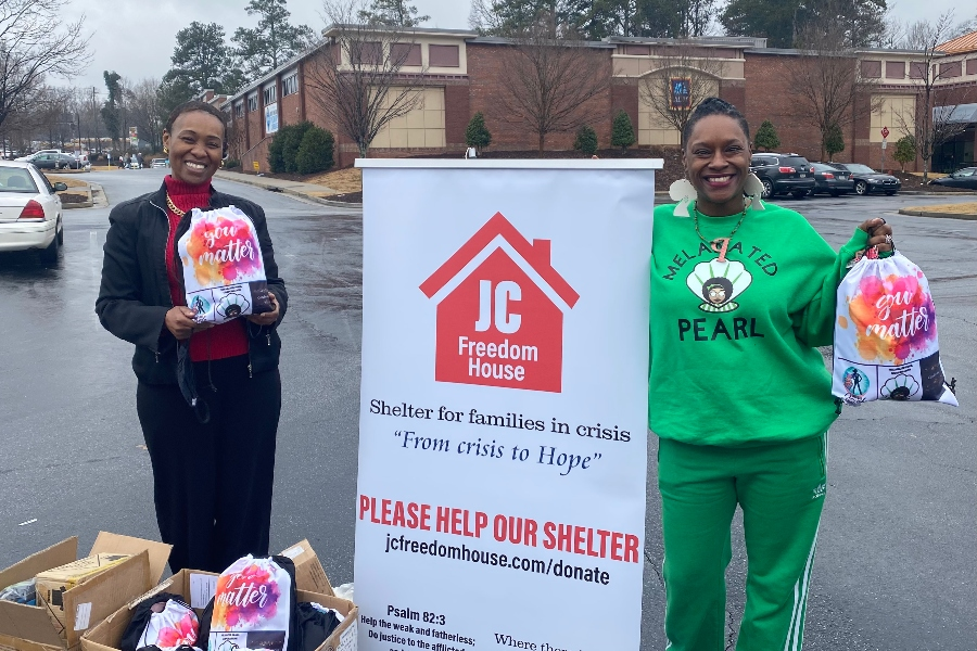 Crystal Perry stands with a Freedom House employee in front of a white sign of the non-profit.