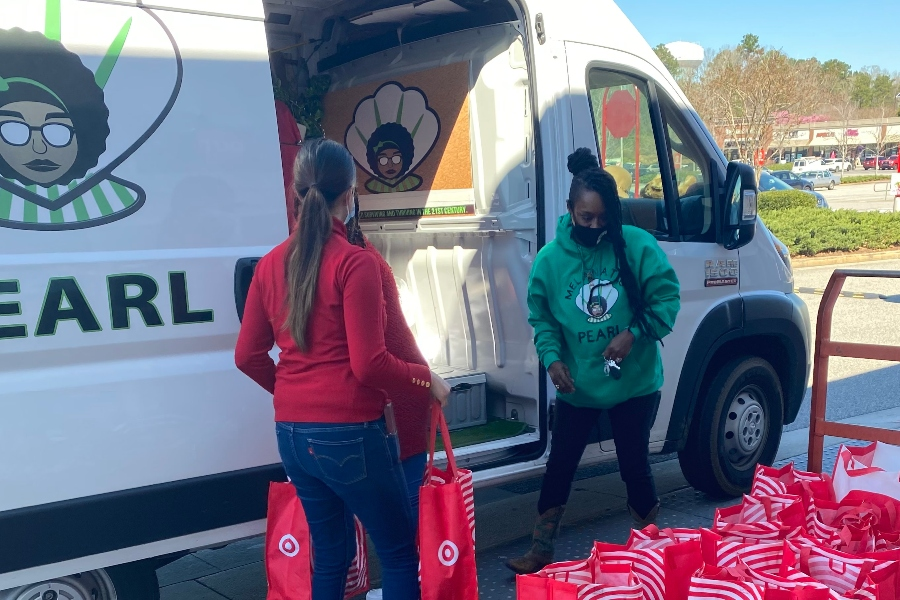 Crystal Perry and a Target employee load her white van for her non-profit Melanated Pearl.