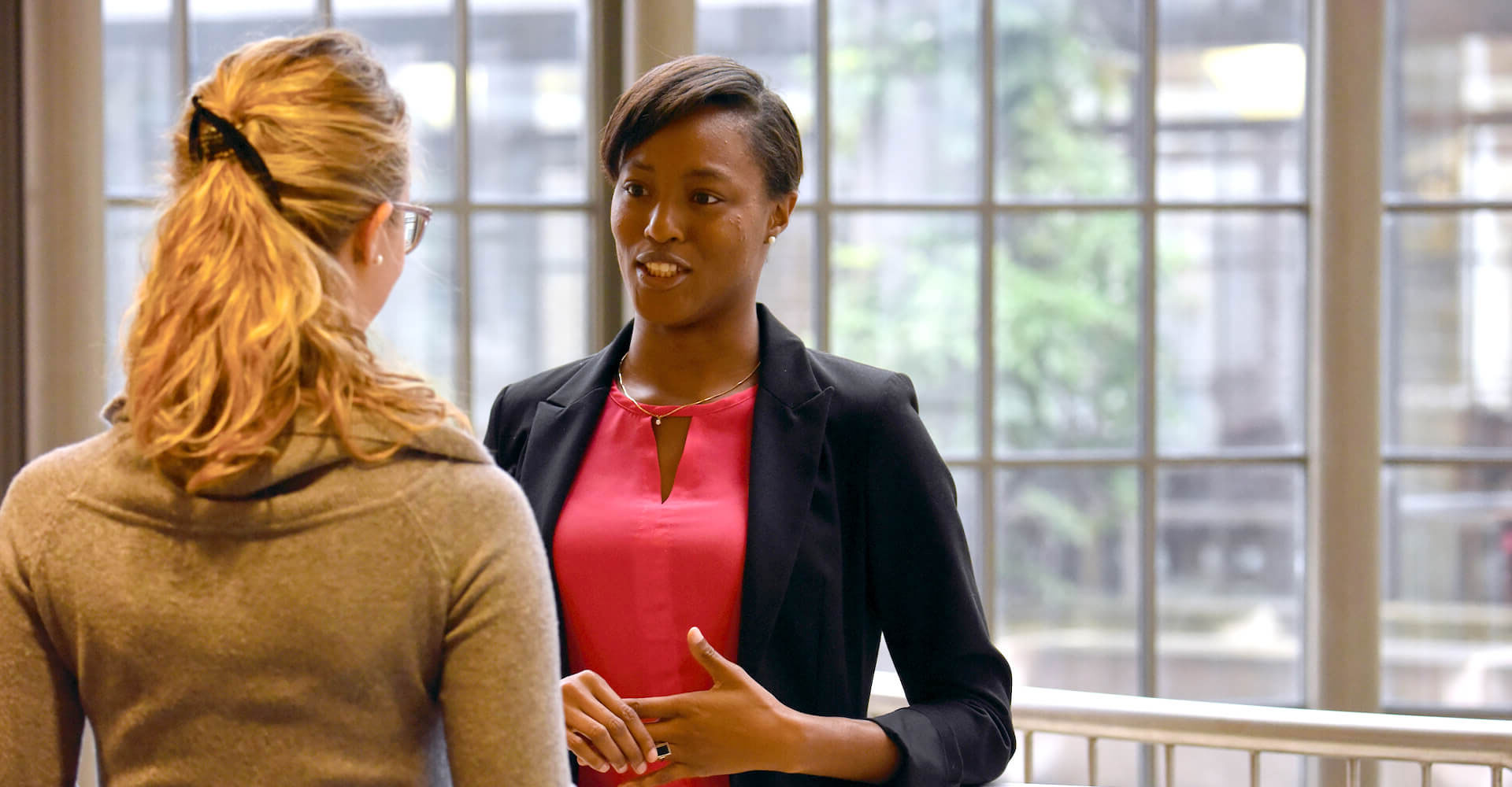 Two women in business attire having a conversation.