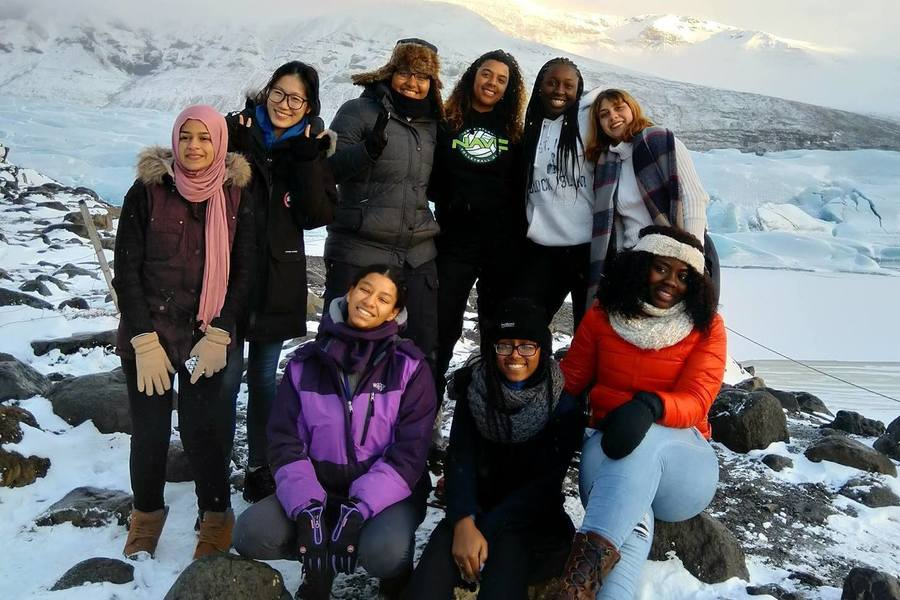 Students pose for group photo in a snowy landscape in Iceland.