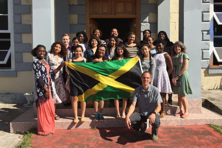 A group of students pose with the Jamaican flag.