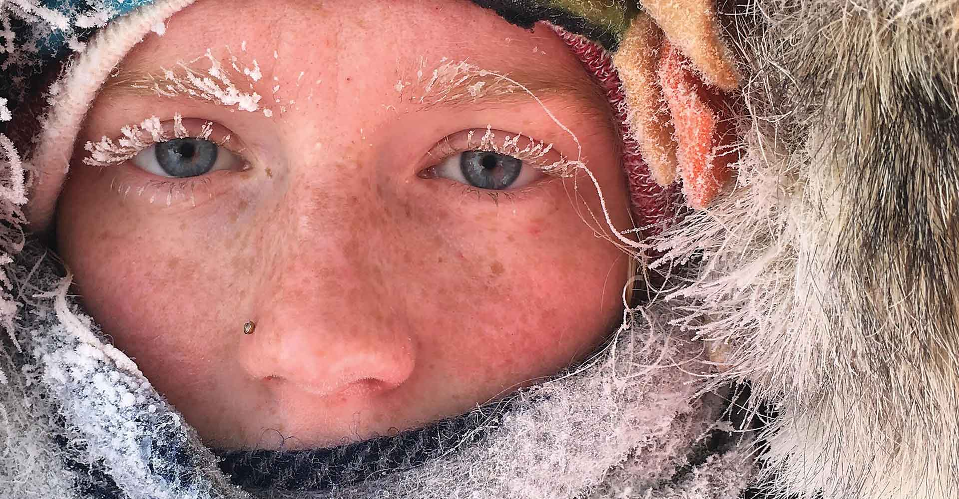 Close up of a face surrounded by a parka with frost on eyelashes and eyebrows.
