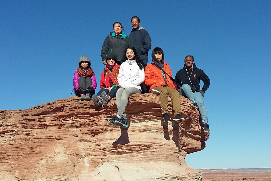 A group of students pose for a photo on a rock formation in the Navajo Nation.