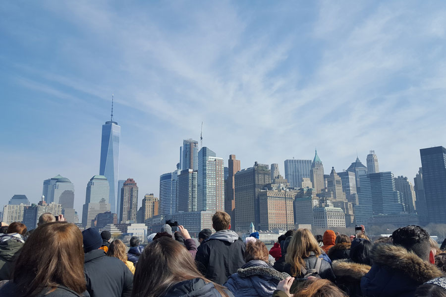 A group of people look at the New York City skyline.